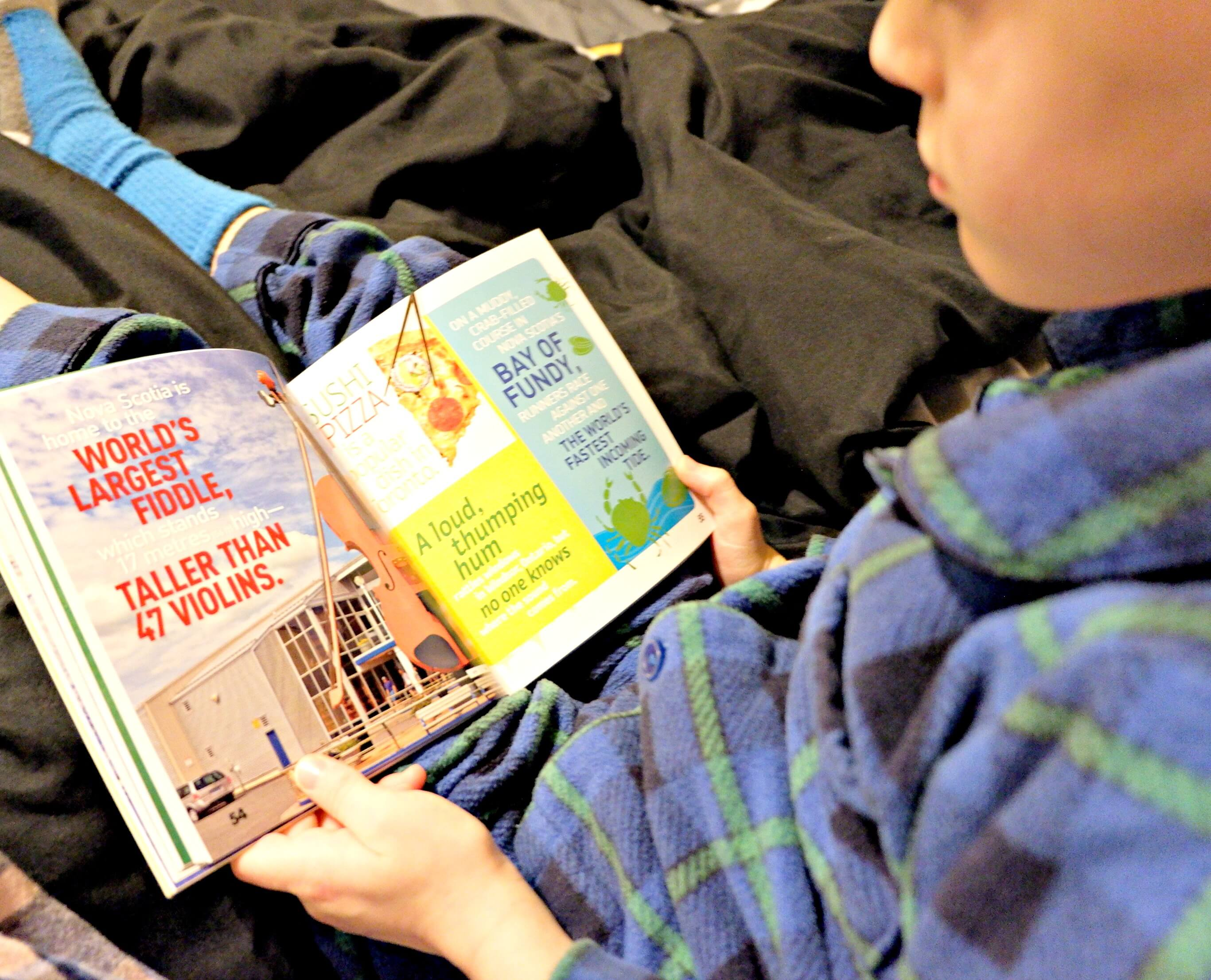 young boy reading in bed national geographic canada facts book weird but true bedtime reading pickle planet